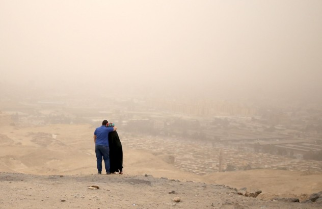 A couple hugs while standing on a hilly area overlooking Cairo on a dusty and hazy day where temperatures reached 114 Fahrenheit, May 27, 2015. REUTERS/Asmaa Waguih