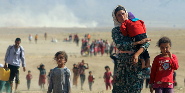 Displaced people from the Yezidi sect, fleeing violence from forces linked to the extremist group Islamic State (also known as ISIS) in the northern Iraqi town of Sinjar, walk towards the Syrian border in August 2014. © 2014 Reuters
