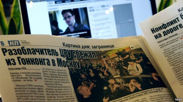 A laptop computer and a newspaper show reports about the arrival of former CIA contractor Edward Snowden to Russia, at Moscow's Sheremetyevo Airport, in June 2013.