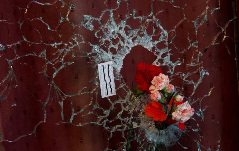 Flowers are put in a window shattered by a bullet as Paris mourns the victims of a terrorist attack. (AP Photo/Peter Dejong)